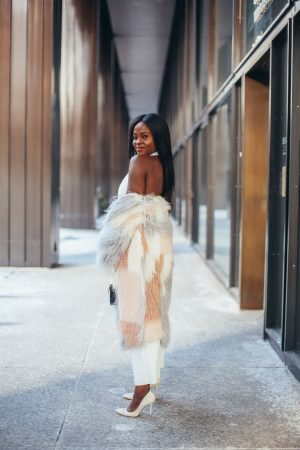 Jennifer Ibe wearing a white jumpsuit and faux fur coat