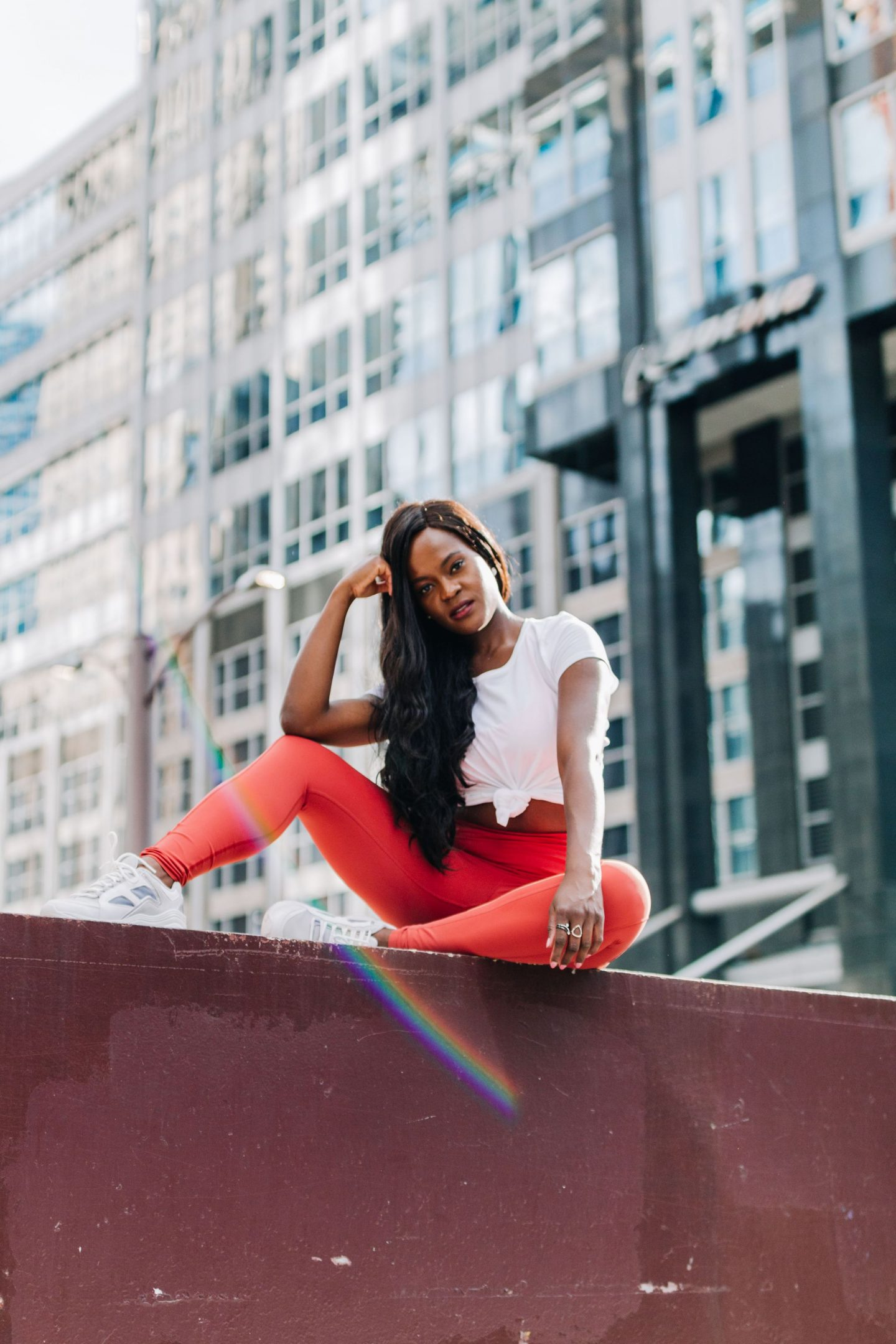 Jennifer Ibe, Cranberry Tantrums wearing lululemon fast and free tight and a white crew III tee and sneakers, sitting on the Chicago bridge